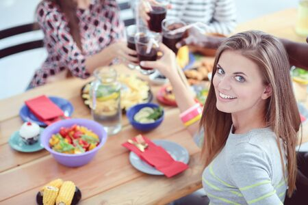 Top view of group of people having dinner together while sitting at wooden table. Food on the table. People eat fast food. Portrait of a girl