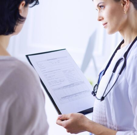 Beautiful female doctor explaining medical treatment to a patient Stock Photo - 129702605