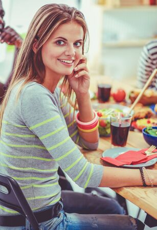 Top view of group of people having dinner together while sitting at wooden table. Food on the table. People eat fast food. The girl is talking on the phone