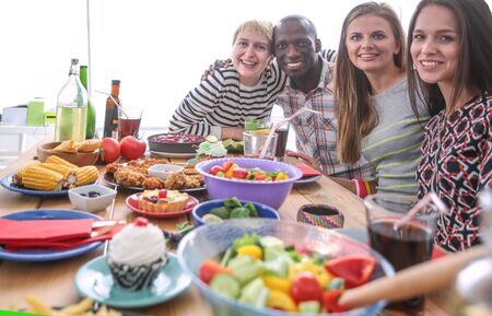 Top view of group of people having dinner together while sitting at wooden table. Food on the table. People eat fast food. Stock Photo - 129702756