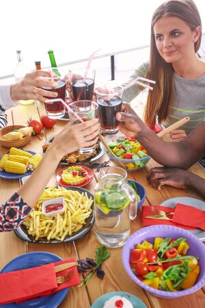 Top view of group of people having dinner together while sitting at wooden table. Food on the table. People eat fast food. Stock Photo - 129702898