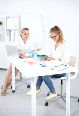 Two women working together at office, sitting on the desk 写真素材
