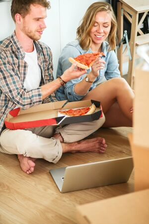 Young couple have a pizza lunch break on the floor after moving into a new home with boxes around them. Young couple Stock Photo