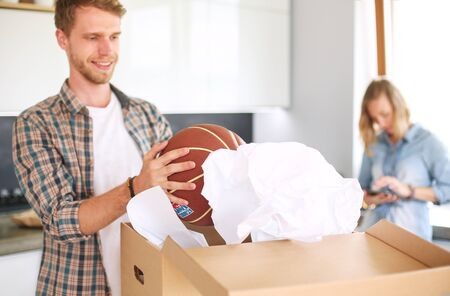 Couple unpacking cardboard boxes in their new home. Young couple. Archivio Fotografico - 129703062
