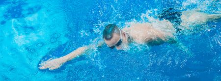 Male swimmer at the swimming pool. Underwater photo. Male swimmer. Stockfoto - 129703149