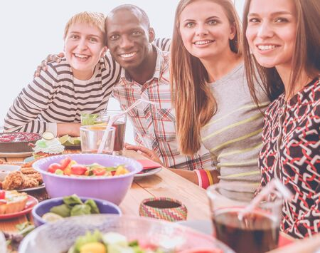 Top view of group of people having dinner together while sitting at wooden table. Food on the table. People eat fast food.