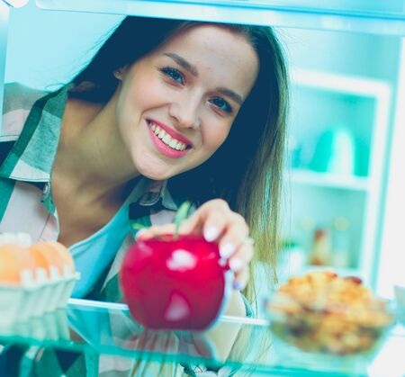 Portrait of female standing near open fridge full of healthy food, vegetables and fruits Stock Photo - 129703647