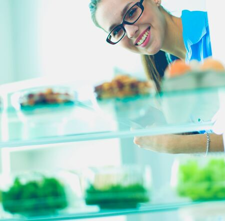 Portrait of female standing near open fridge full of healthy food, vegetables and fruits Stock Photo - 129703653