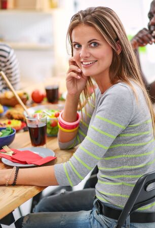 Top view of group of people having dinner together while sitting at wooden table. Food on the table. People eat fast food. The girl is talking on the phone Stock Photo - 129703660