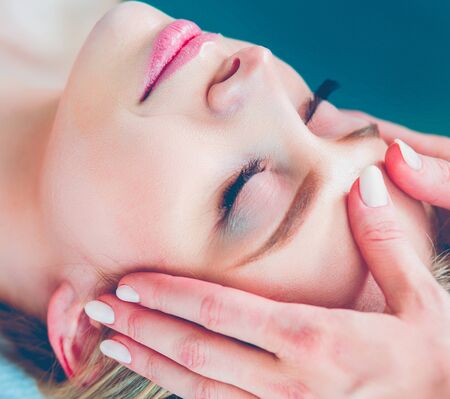 Young woman lying on a massage table,relaxing with eyes closed. Woman. Spa salon 写真素材