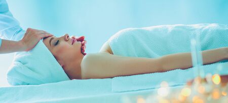 Young woman lying on a massage table,relaxing with eyes closed. Woman. Spa salon Stockfoto