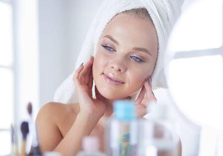 Junge Frau im Bademantel, der im Badezimmerspiegel schaut