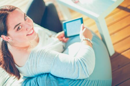Smiling young woman sitting on sofa with touchpad.