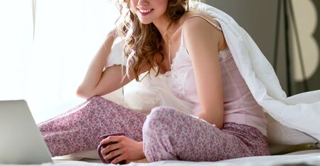 Young beautiful woman sitting in bed with laptop. Stock Photo