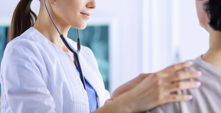A female doctor listening a patient with a stethoscope