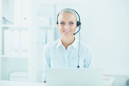 Portrait of pretty young female operator sitting at office desk with headset Stok Fotoğraf