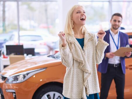 Young beautiful woman is very happy after buying a new car