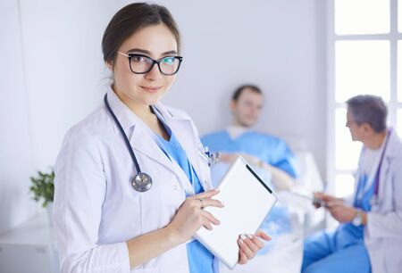 Female doctor using tablet computer in hospital lobby