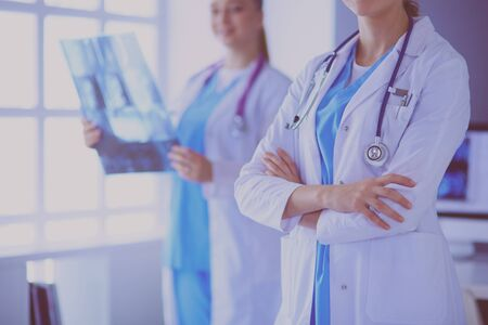 Close up shoot of doctors crossed hands and colleague with x-ray on the background.