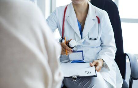 Portrait of doctor explaining bottle of medicine to her patient Stok Fotoğraf - 130558236