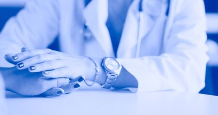 Woman doctor helping senior holding hand in hospital Foto de archivo - 130558469
