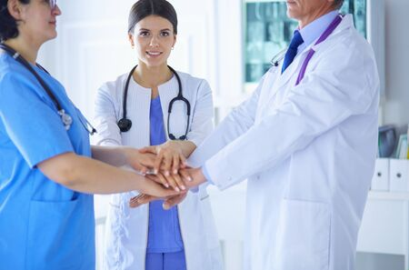Group of doctors putting their hands together