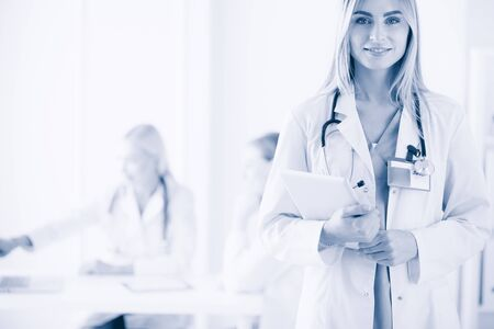 portrait of a young female doctor, with aipads in hand, in a medical office