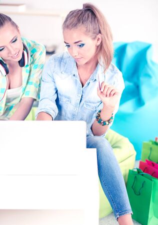 Two young female sisters sitting on sofa, in the living room, at home, making shopping online on digital tablet, holding a credit card Banco de Imagens