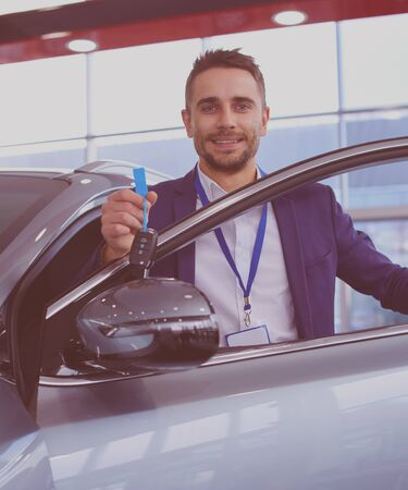 Dealer stands near a new car in the showroom 스톡 콘텐츠