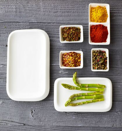 various ground spices in bowl on old wooden table with asparagus