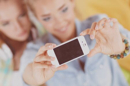 Cheerful young girls do selfie in cafe