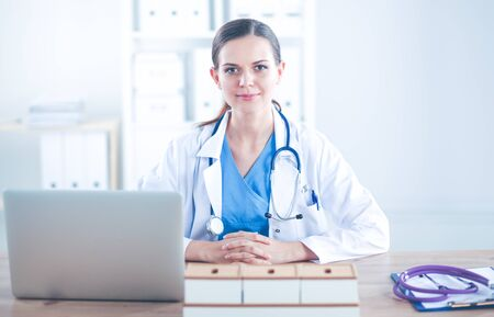Beautiful young smiling female doctor sitting at the desk and writing. female doctor