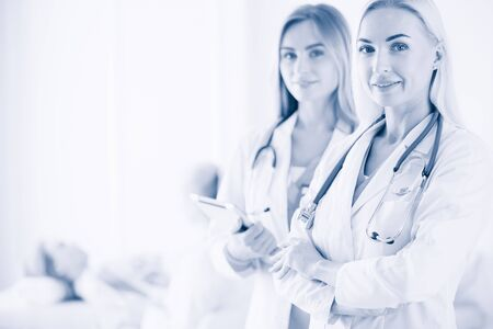Portrait of three confident female doctors standing with arms crossed at the medical office. Banco de Imagens