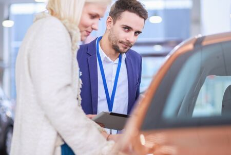 Dealer with woman stands near a new car in the showroom 스톡 콘텐츠