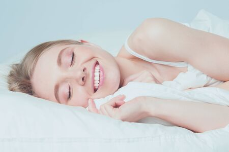Photo of sleeping young woman lying in bed with eyes closed