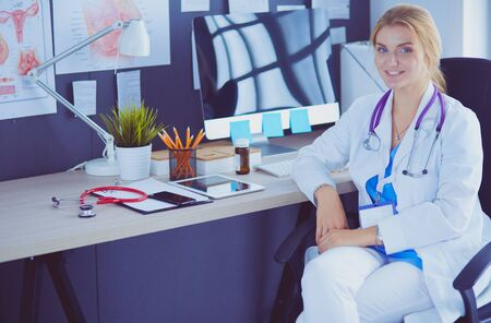 Portrait of young female doctor sitting at desk in hospital