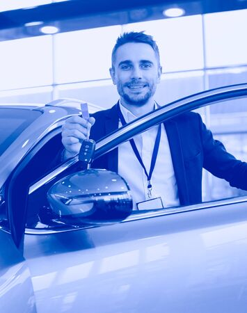 Dealer stands near a new car in the showroom Stockfoto