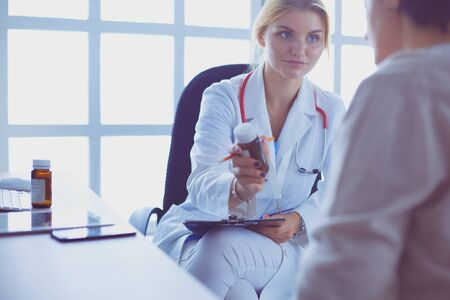 A doctor is talking and examining a patient 写真素材