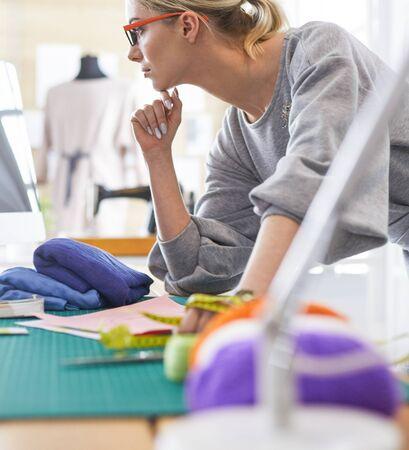 Ein Porträt einer jungen asiatischen Designerin, die einen Laptop benutzt und lächelt, Kleidung als Hintergrund gehängt