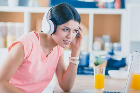 Portrait of a cheerful young woman listening to music with headphones and using laptop computer while standing at the kitchen