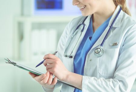 Doctor with a stethoscope, holding a notebook in his hand. Close-up of a female doctor filling up medical form at clipboard while standing straight in hospitalDoctor with a stethoscope, holding a note 스톡 콘텐츠