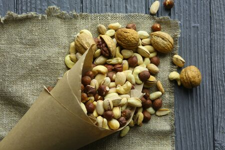 Mix of different nuts in a paper cup against the background