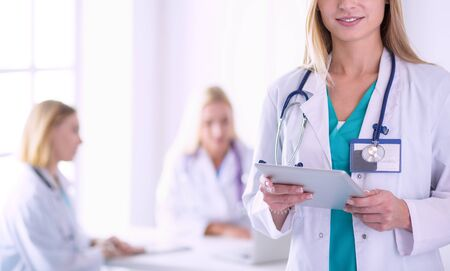 portrait of a young female doctor, with aipads in hand, in a medical office.