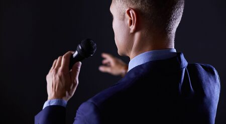 Portrait of a businessman standing with a microphone and looking ahead, speak at the conference.