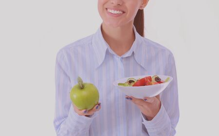 Portrait of a beautiful woman doctor holding a plate with fresh vegetables and green apple. Woman doctor.