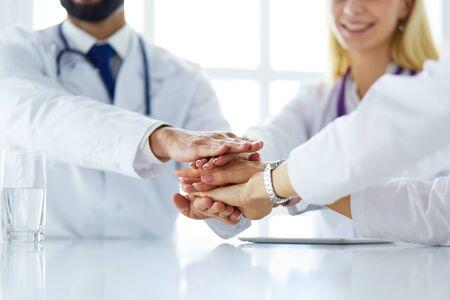 Team of doctors putting hands together, closeup.