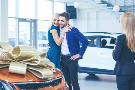 A man makes a gift - a car to his wife. She is surprised at this. They are very happy about 写真素材