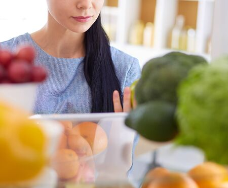 Smiling woman taking a fresh fruit out of the fridge, healthy food concept.