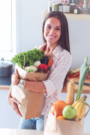 Young woman holding grocery shopping bag with vegetables. Young woman Imagens