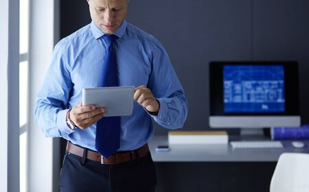Smiling businessman with touchpad standing at workplace in office Stock fotó
